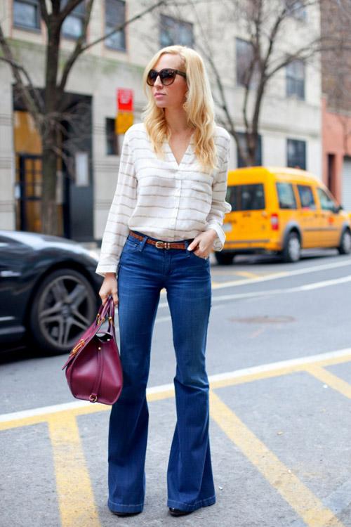 Девушка в белой блузке и в джинсах клеш
