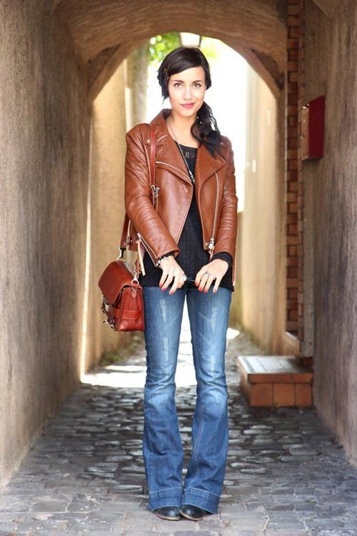 Девушка в коричневой косухе и джинсах клеш