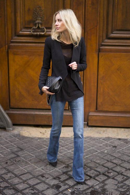 Девушка в серо-синих джинсах клеш и темном жакете