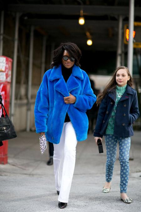 Девушка в белых брюках, черной водолазке и яркая синяя шуба с коротким ворсом