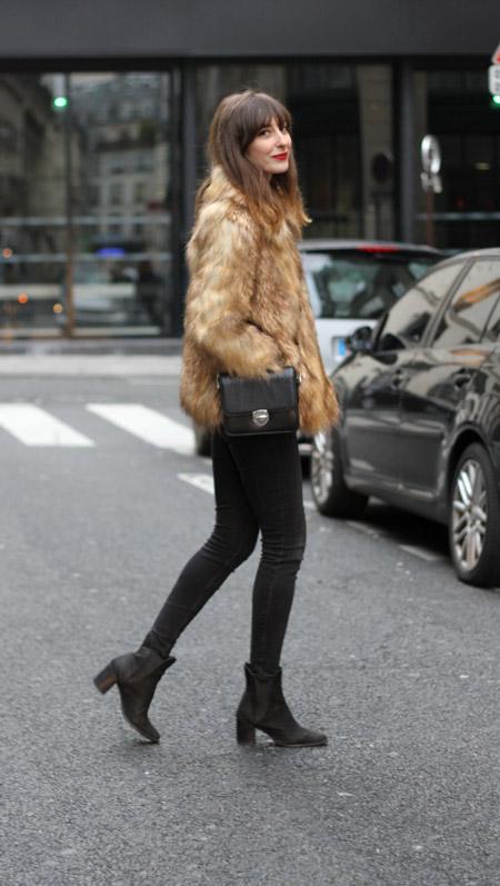 Девушка в коричневой короткой шубе , черных джинсах и полусапогах