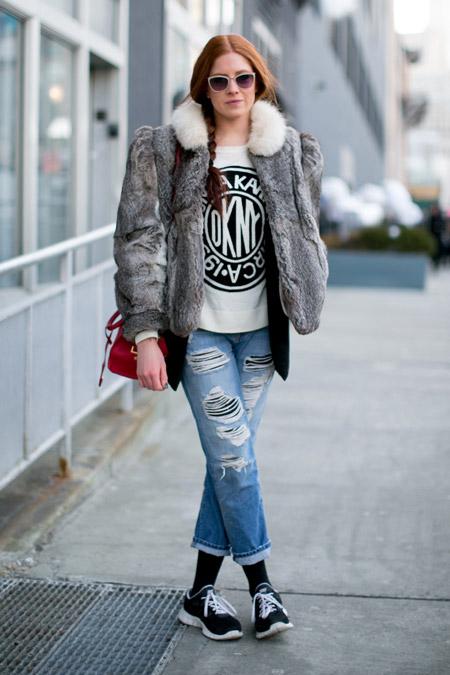 Девушка в рванных джинсах и серой шубке с коротким верхом