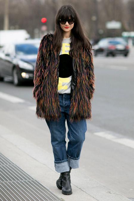 Девушка в широких джинсах и черной меховой шубе с разноцветными ворсинками