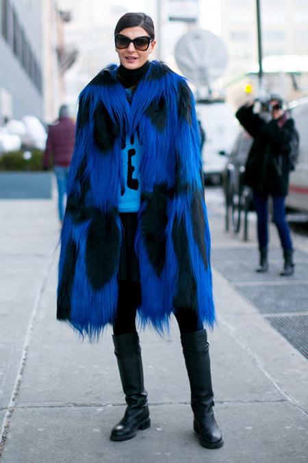 Девушка в синей шубе с черными пятнами и длинным ворсом