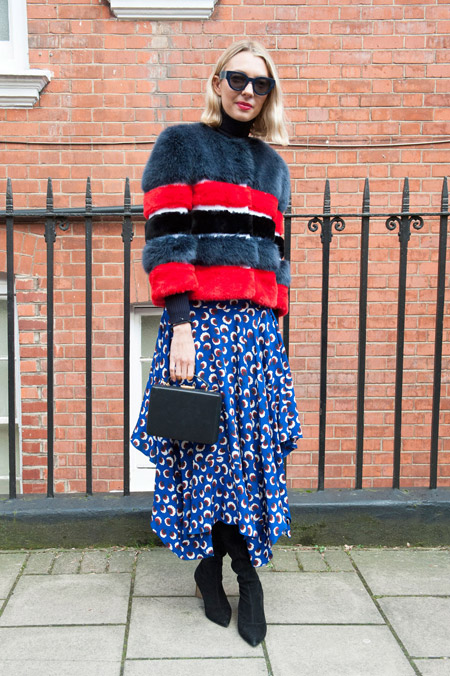 Девушка в синей юбке с принтом и красно-серой меховой шубке