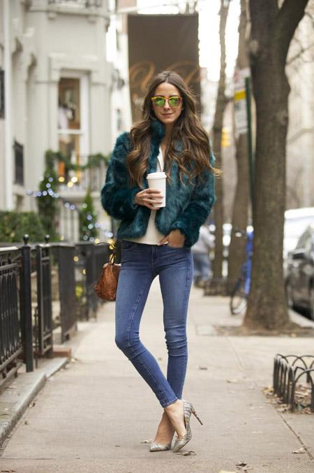 Девушка в синих джинсах, белой футболке и коротенькой зеленой шубке