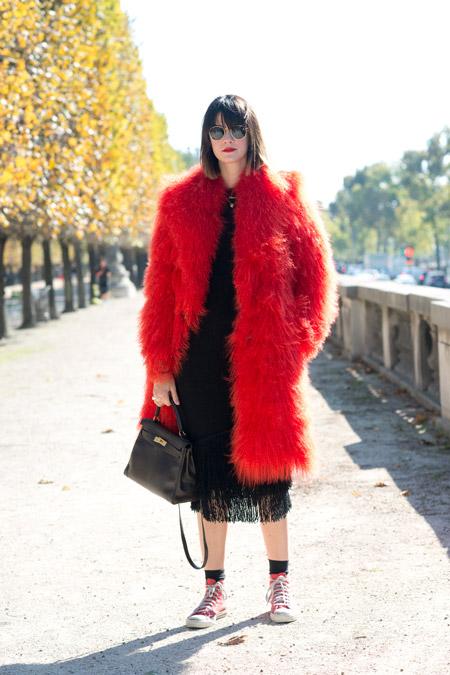 Модель в черном платье с кедами и красной меховой шубе