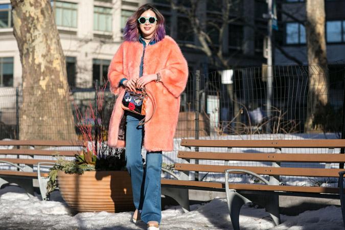 Модель в расклешенных джинсах и оранжевой меховой шубе