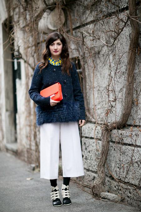 Модель в широких бермудах и синем пальто с мехом