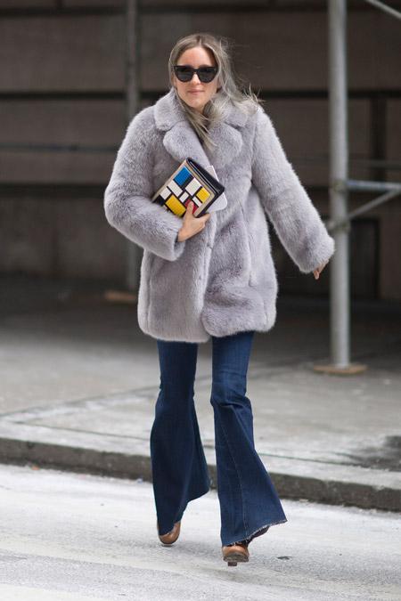 Модель в синих расклешенных джинсах и серой меховой шубе