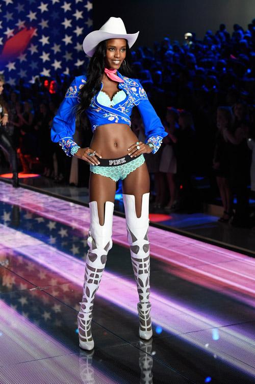 Модель в высоких белых сапогах, голубом нижнем белье и синей кофте, белая шляпа