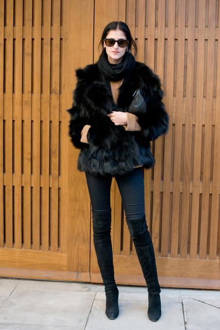 На девушке черные сапоги выше колен, джегинсы и черная меховая шубка