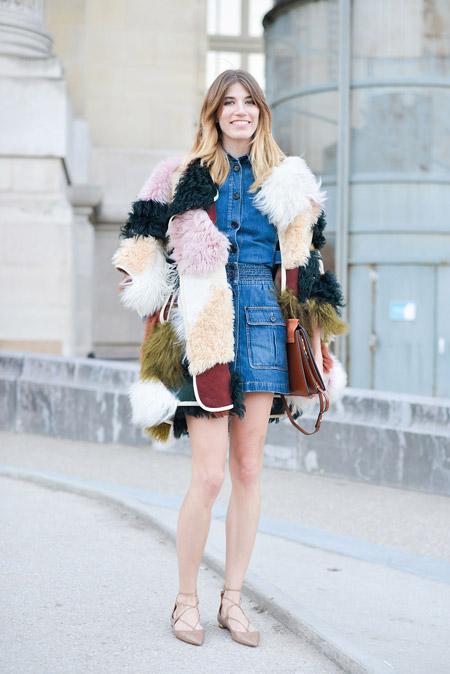 На девушке джинсовая мини юбка и рубаха, разноцветная меховая шубка