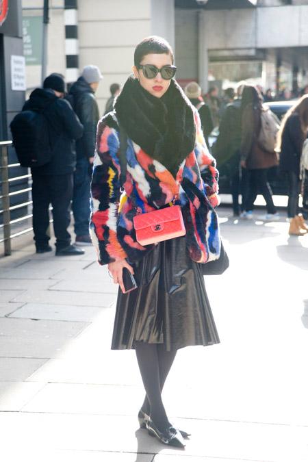 На девушке кожанная юбка миди и разноцветная короткая шубка
