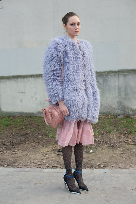 На модели ажурные чулки, нежная розовая юбка и большая серая шуба
