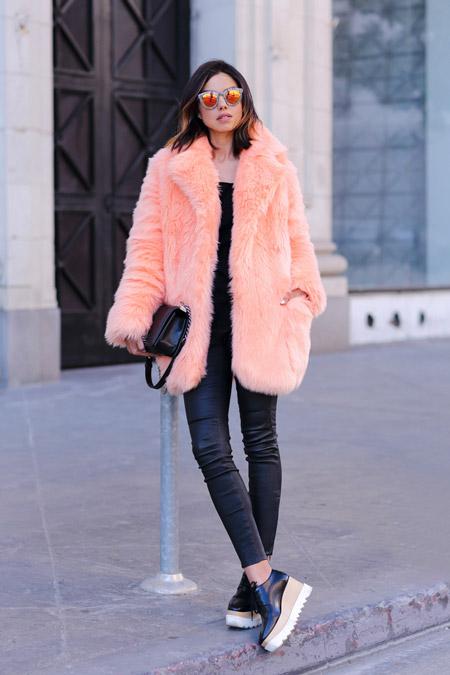 На модели черные джегинсы, ботинки на толстой платформе и розовая меховая шуба