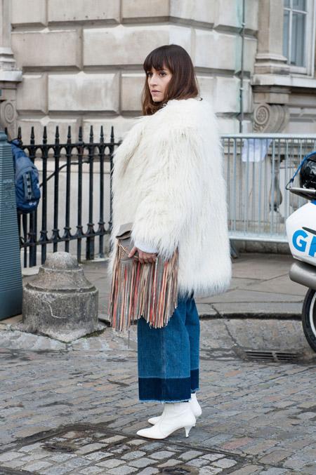 На модели широкие джинсы и белая меховая шуба с длинным ворсом