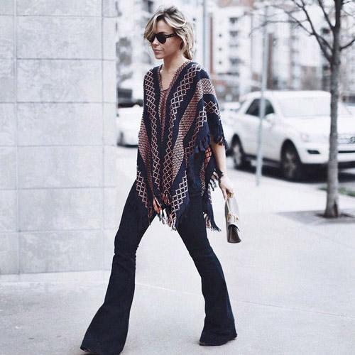 Девушка в пончо и джинсах клеш