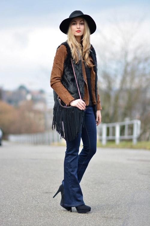 Девушка с сумкой с бахромой и джинсах клеш