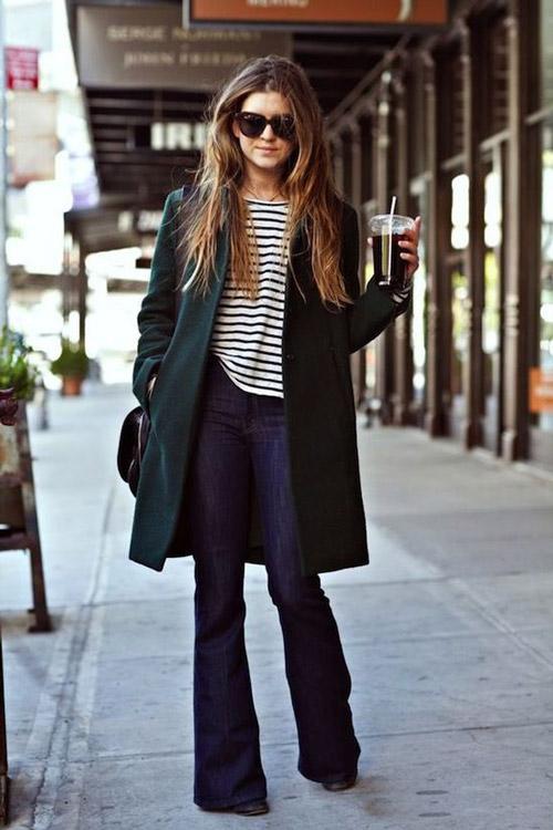 Девушка в зеленом пальто и джинсах клеш
