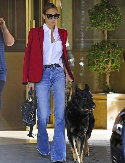Девушка в бордовом пиджаке и синих джинсах клеш