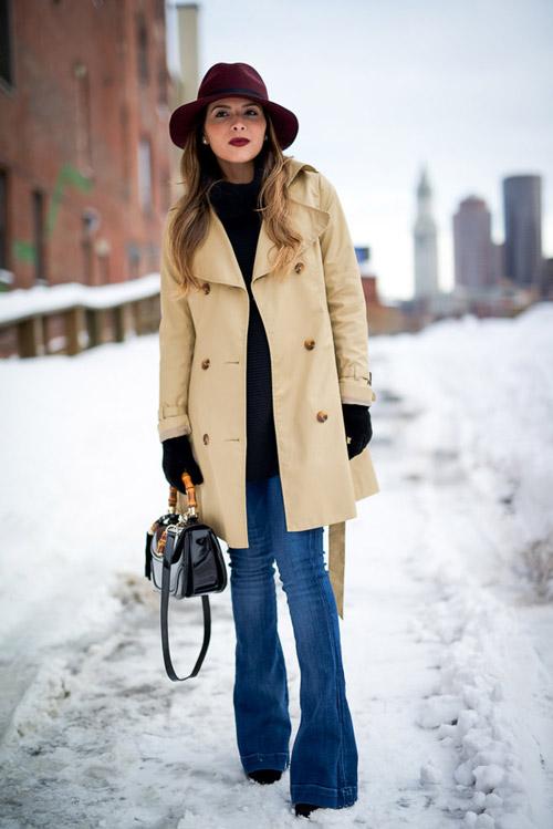 Девушка в бежевом пальто и джинсах клеш