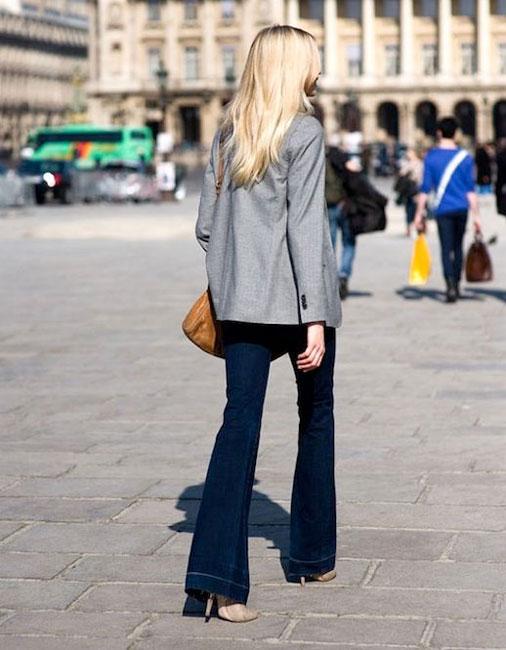 Девушка в темно-синих джинсах клеш и сером пиджаке с коричневой сумкой