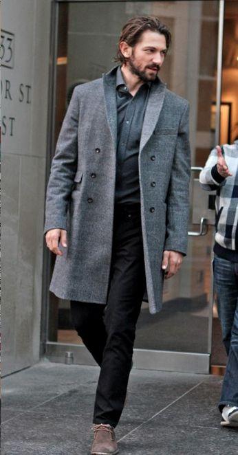 мужчина в черных джинсах и сером пальто