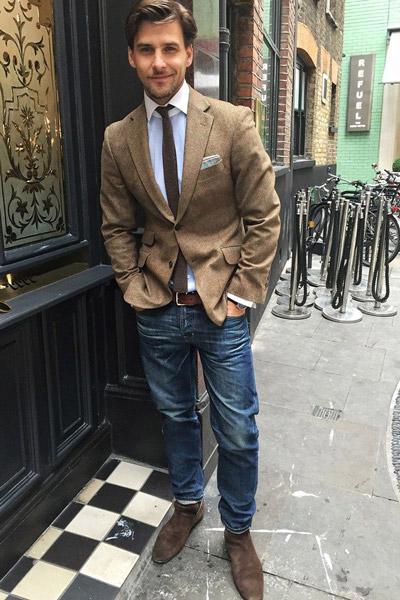 мужчина в джинсах и бежевом пиджаке с галстуком