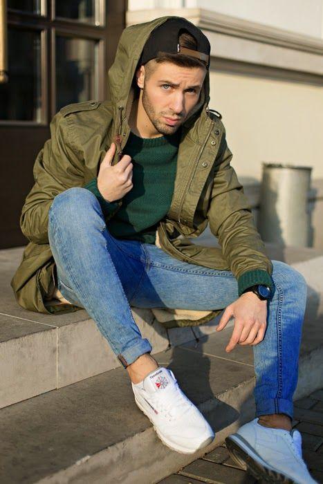 мужчина в голубых джинсах, кроссовках и куртке
