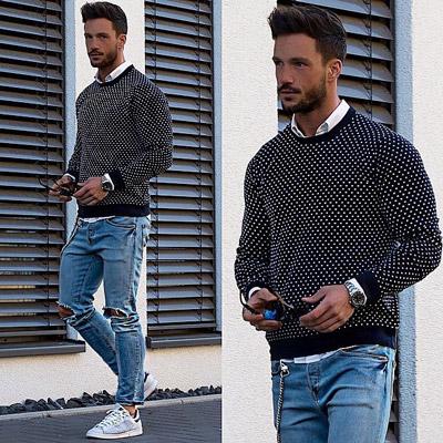 мужчина в голубых рваных джинсах и пуловере