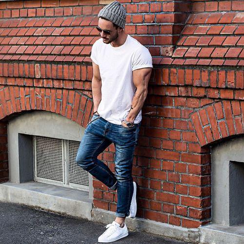 мужчина в рваных джинсах и белой майке с шапкой