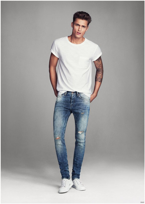 мужчина в зауженных джинсах, белой майке и кедах