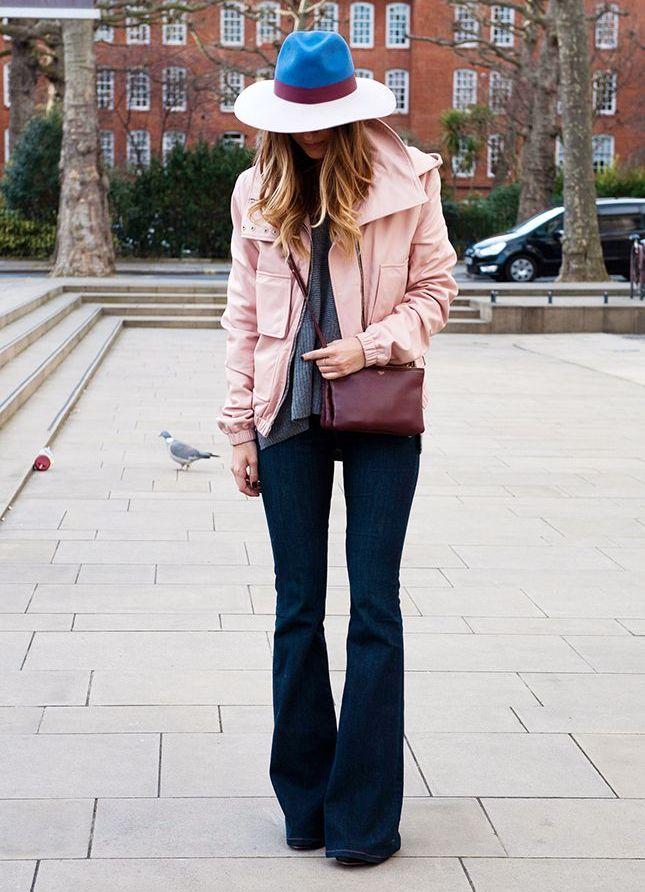 Девушка в розовой куртке, шляпе и джинсах клеш