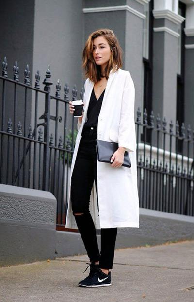 Девушка в белом пальто и черных джинсах