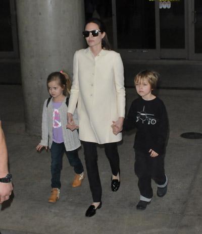 Анджелина Джоли в черных брюках и пальто молочного цвета прямого покроя