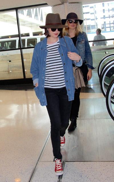 Дакота Джонсон в темных джинсах, тельняшка, джинсовая рубашка, красно-белын кеды и шляпа