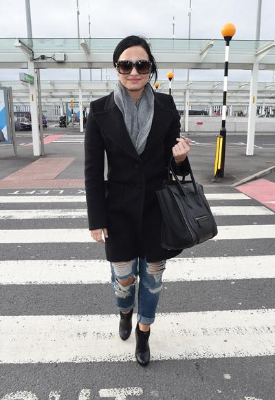 Деми Ловато в аэропорту в рванных синих джинсах, черном пальто на пуговицах и серый шарф