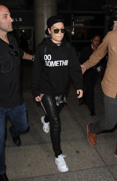 Джесси Джей в аэропорту в кожанных брюках, кроссовки и черная толстовка, кепка