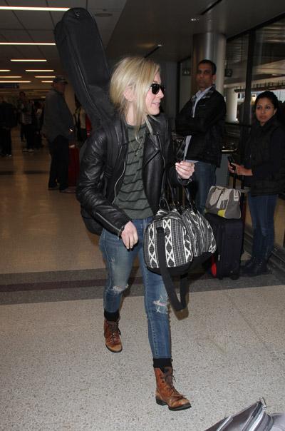 Эмили Кинни в аэропорту одета в рванные синие джинсы, серая кофта и черная куртка косуха