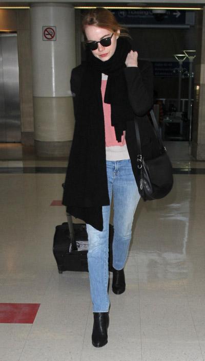Эмма Стоун в голубых джинсах, черное пальто, шарф и ботинки