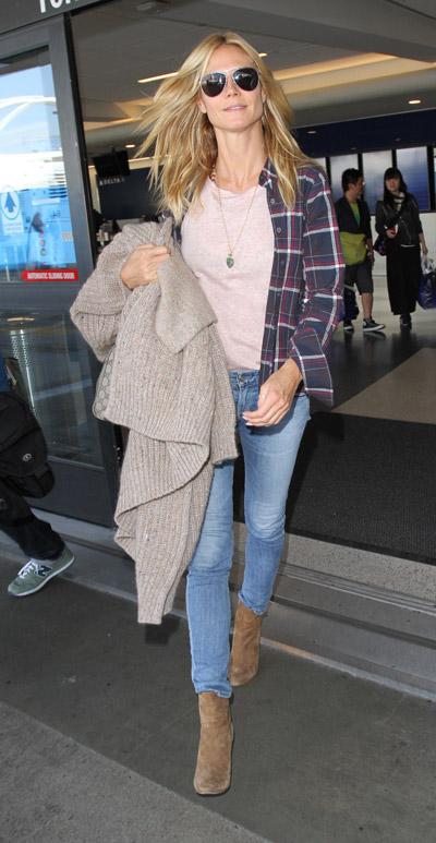 Хайди Клум в аэропорту, одетая в узкие голубые джинсы, персиковая футболка и рубаха в клетку
