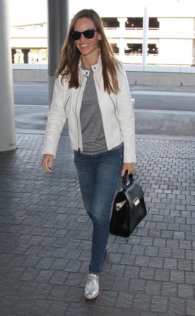 Хилари Суонк в синих джинсах, серая футболка и белая куртка, черная объемная сумка