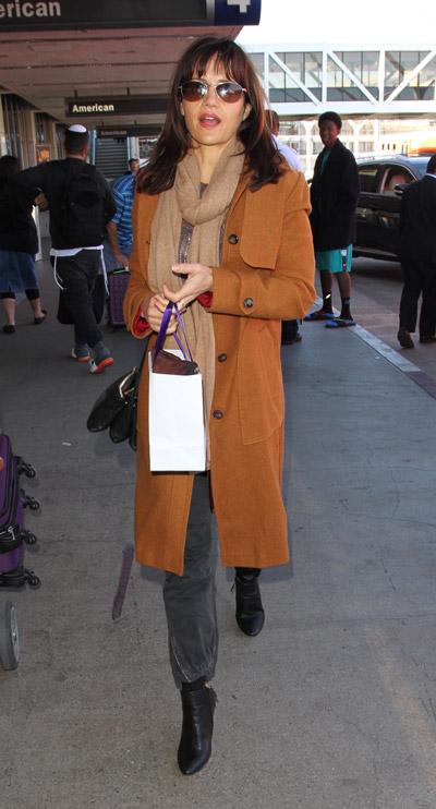 Карла Гуджино в аэропорту в серых джинсах, длинное коричневое пальто и шарф