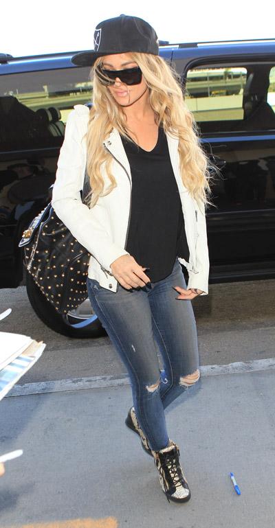 Кармен Электра в рваных джинсах, черной футболке, белой куртке и черная кепка