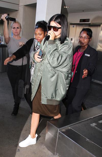 Кайли Дженнер в аэропорту в коричневой юбке по колено и серой куртке