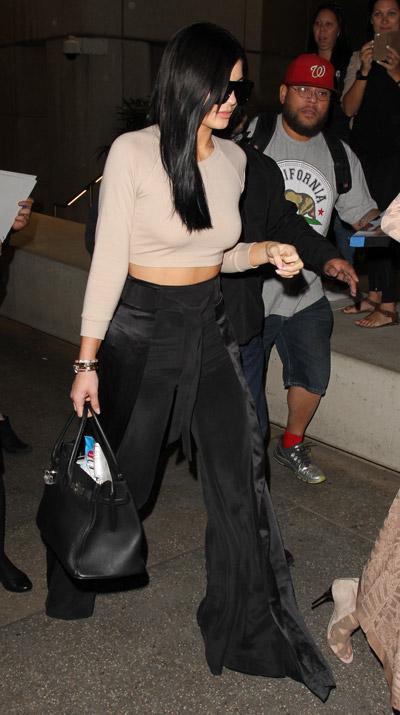 Кендалл Дженнер в расклешенных черных брюках и кроп топ телесного цвета