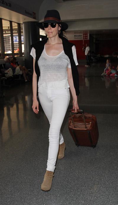 Лора Препон белых брюках, футболке, черная шляпа и коричневые ботильоны
