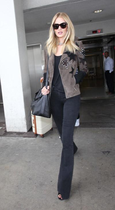 Роузи Хантингтон Уайтли в аэропорту в черных расклешенных брюках, футболка и коричневыя куртка, сумка
