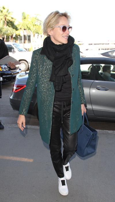 Шэрон Стоун в кожанных брюках, пальто с зеленым оттенком, черный шарф и синяя шапка